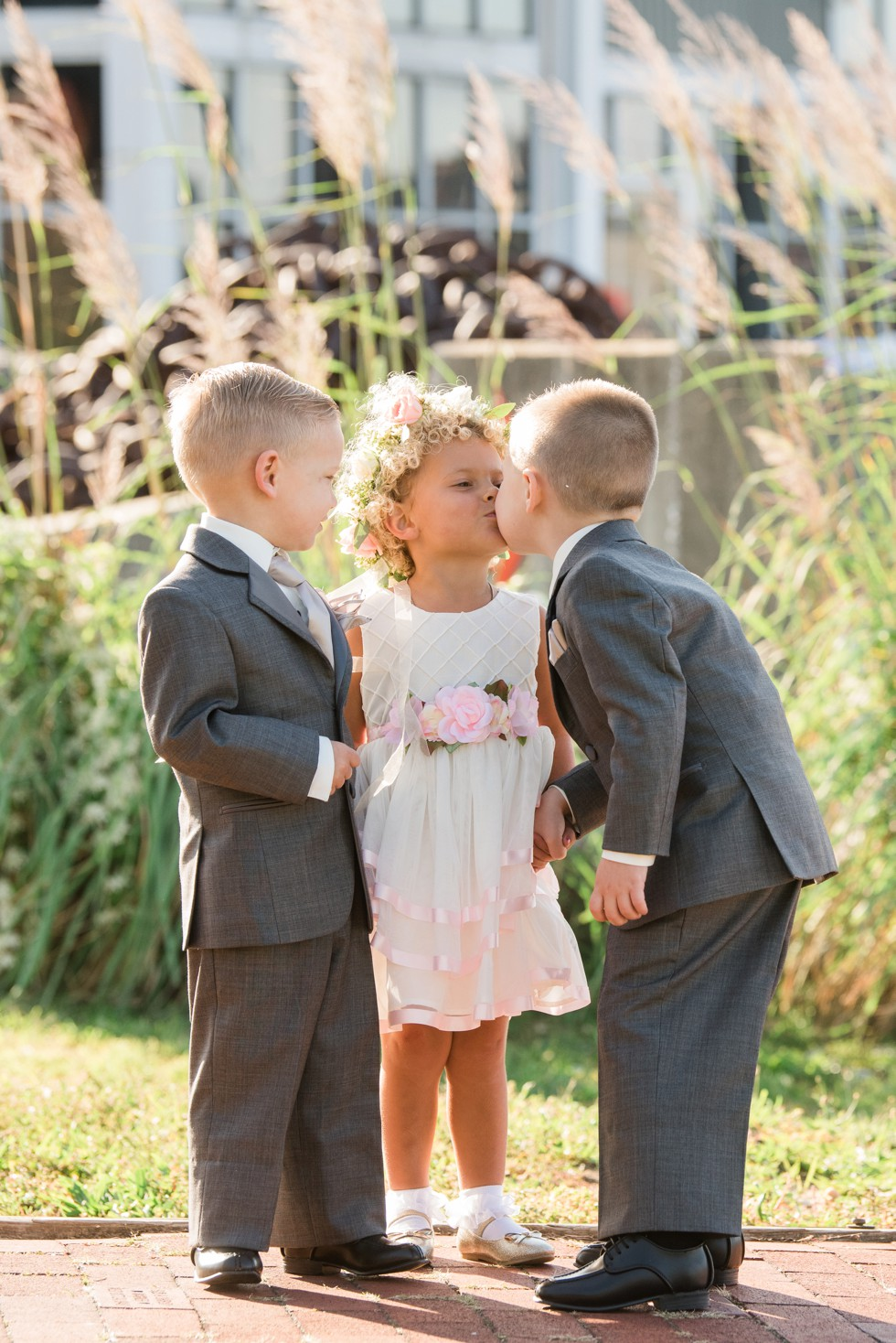 Ring bearer kissing flower girl in the sunshine and grey suits