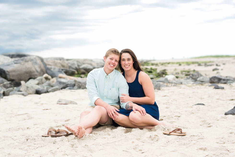 Two brides sitting in the sand on the Jersey Shore of Barnegat Lighthouse