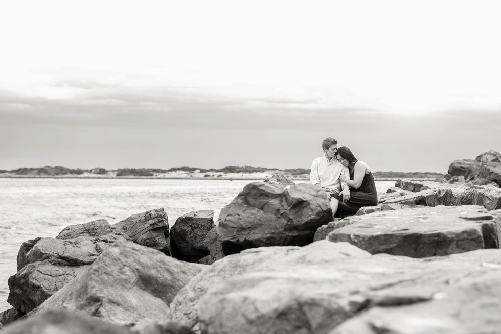 Couple in love on the rocks of the jersey shore beach at Barnegat light