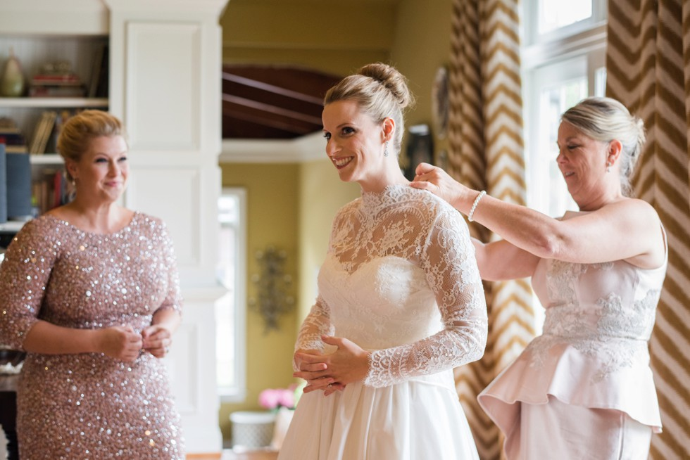 Bride getting into her WTOO by Watters strapless bridal gown with lace coverlet