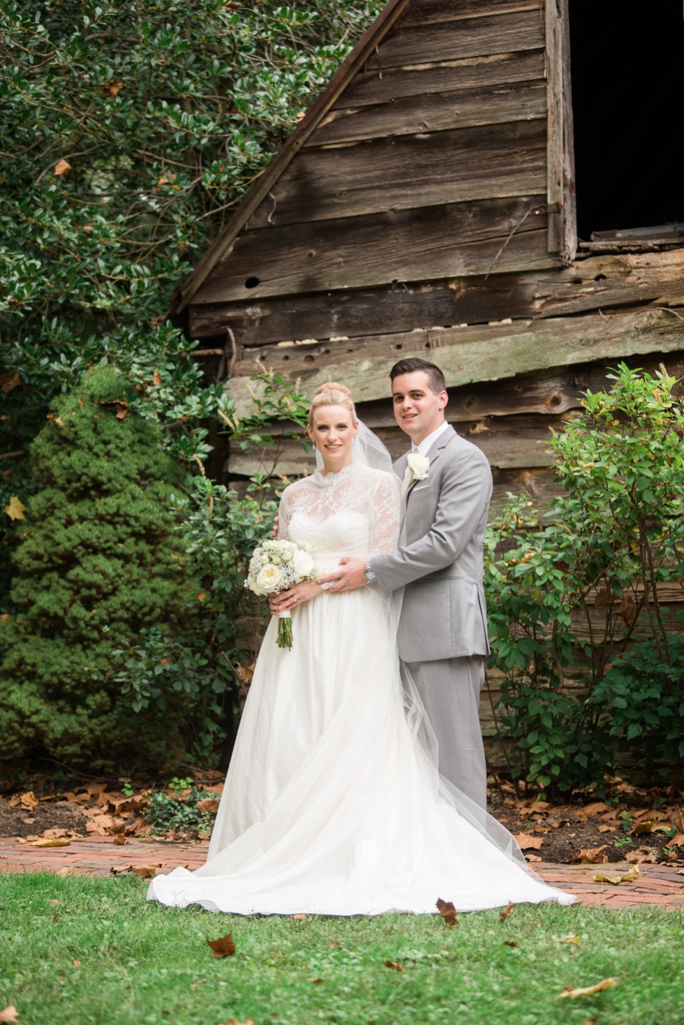 Bride and Groom kissing in front of the wood cabin at Elkridge Furance Inn