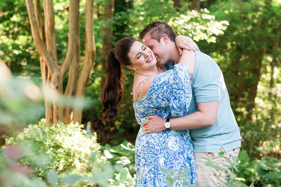 Couple in blue snuggling up in the trees in Annapolis for engagement photos