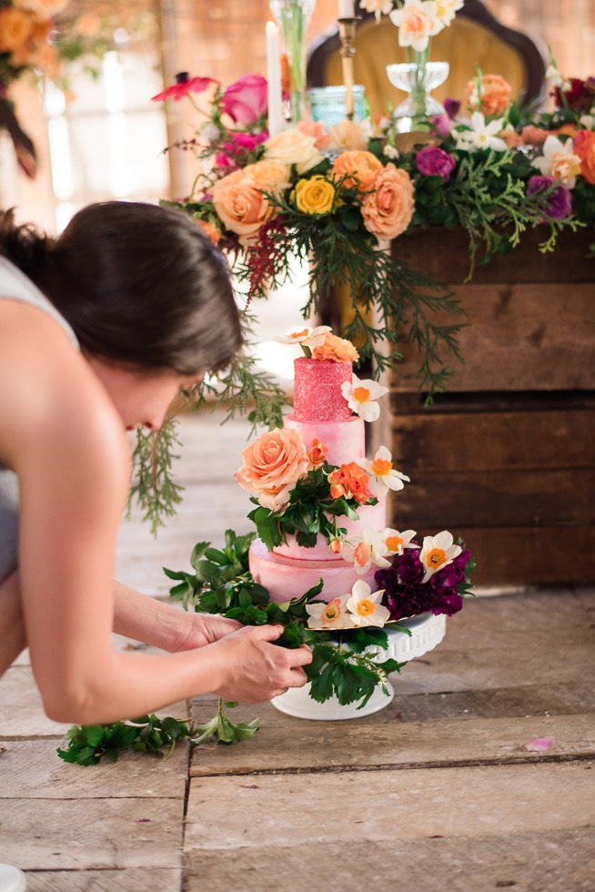 pastry chef adding flower details to wedding cake
