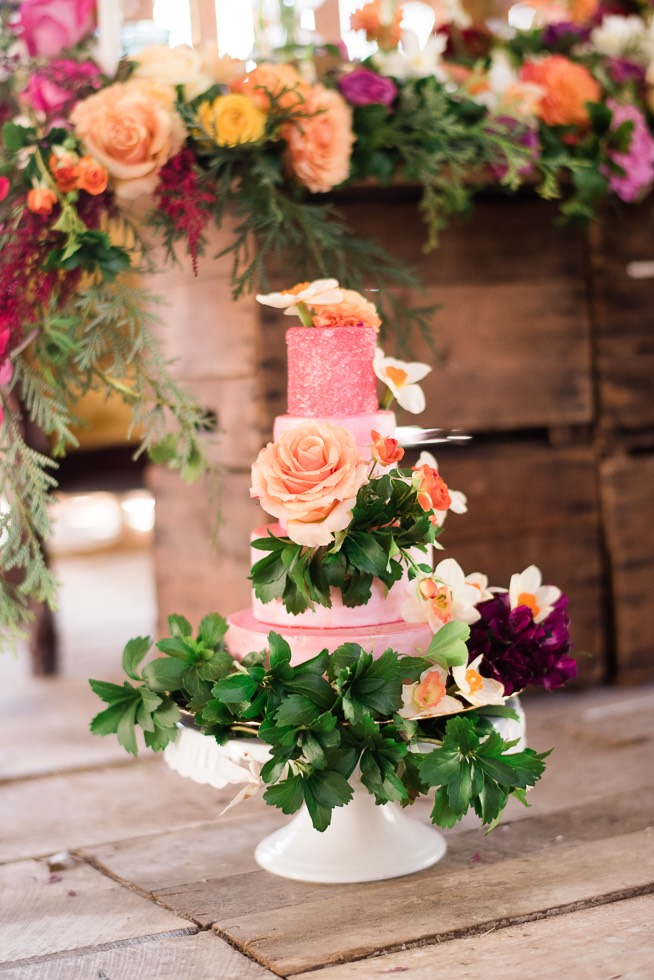 pink wedding cake with flowers and greenery