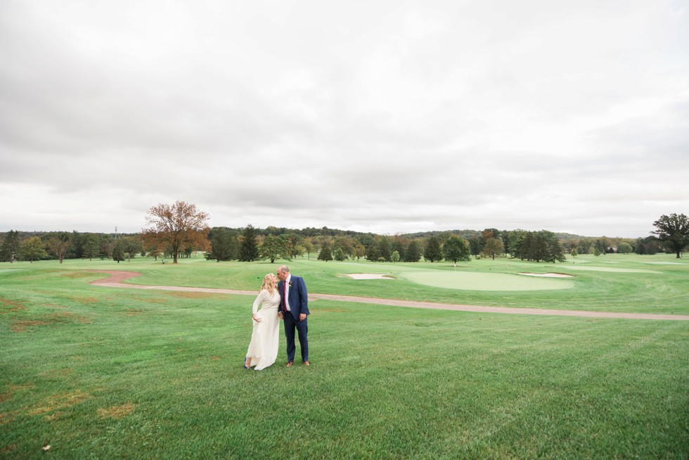 Bride and groom walking on golf course in the fall