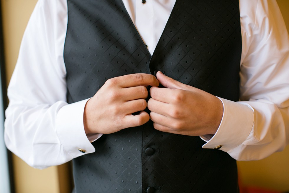 groom getting ready buttoning tux