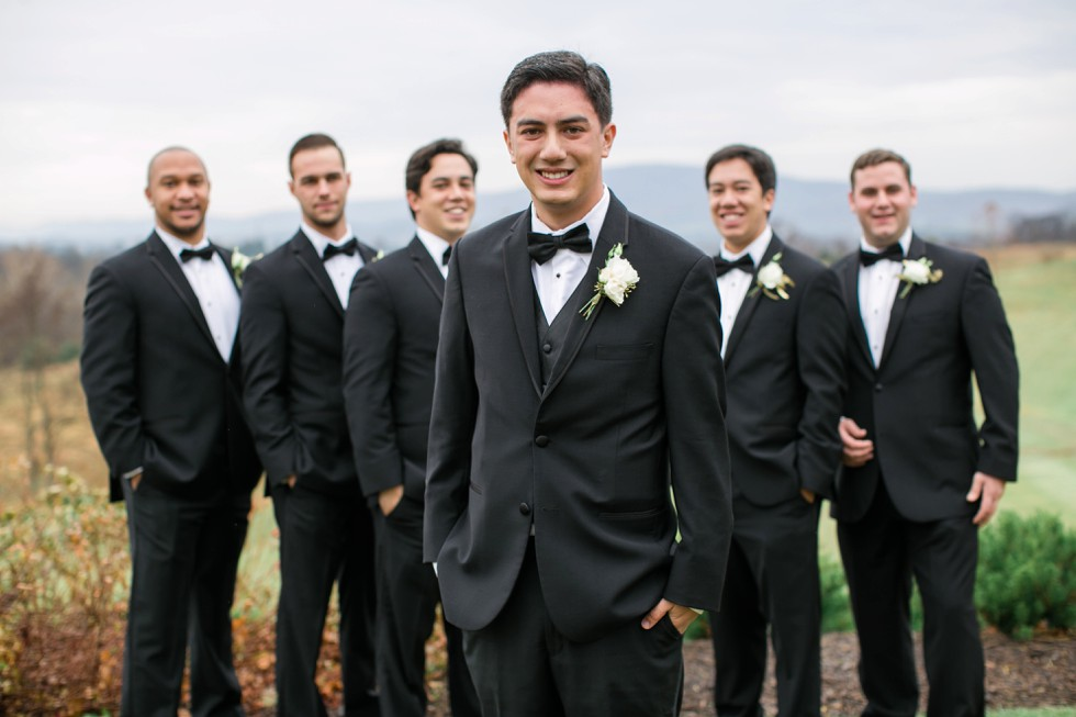 groomsmen in black tuxes on a mountain