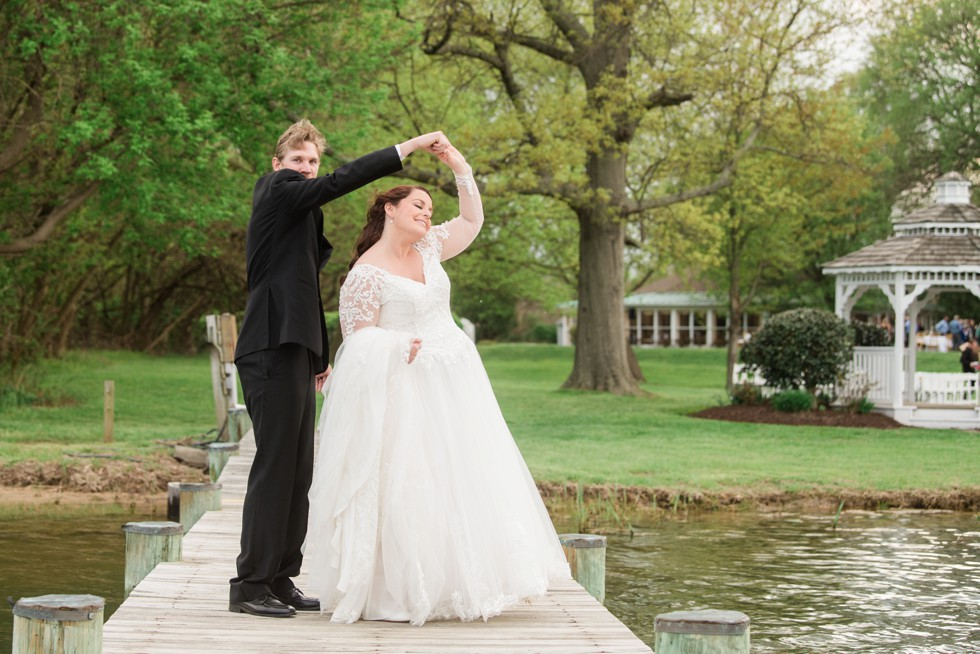 bride and groom dancing on a dock