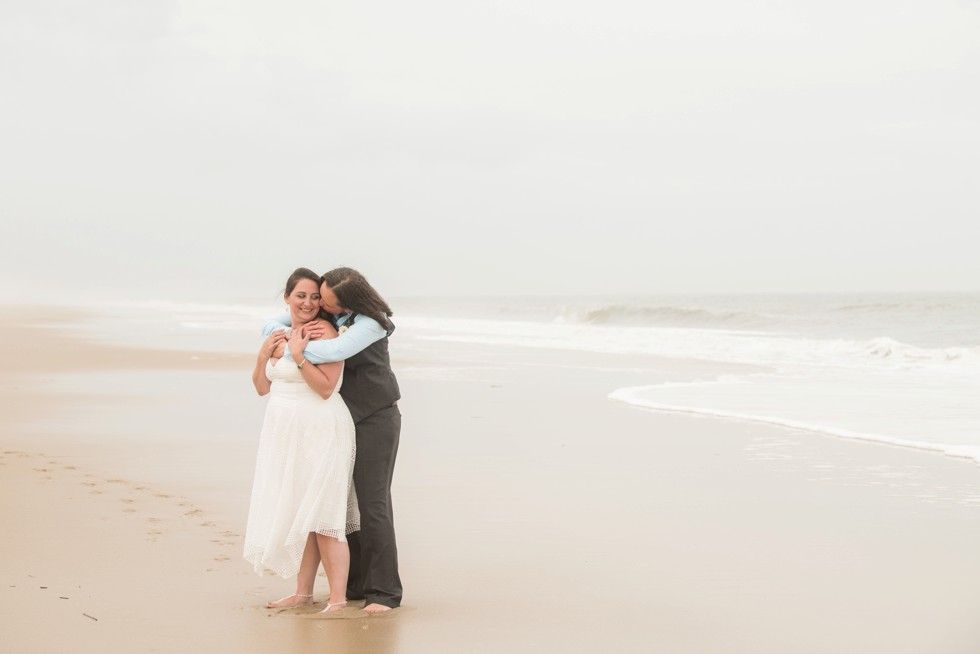 Brides snuggling on the beach