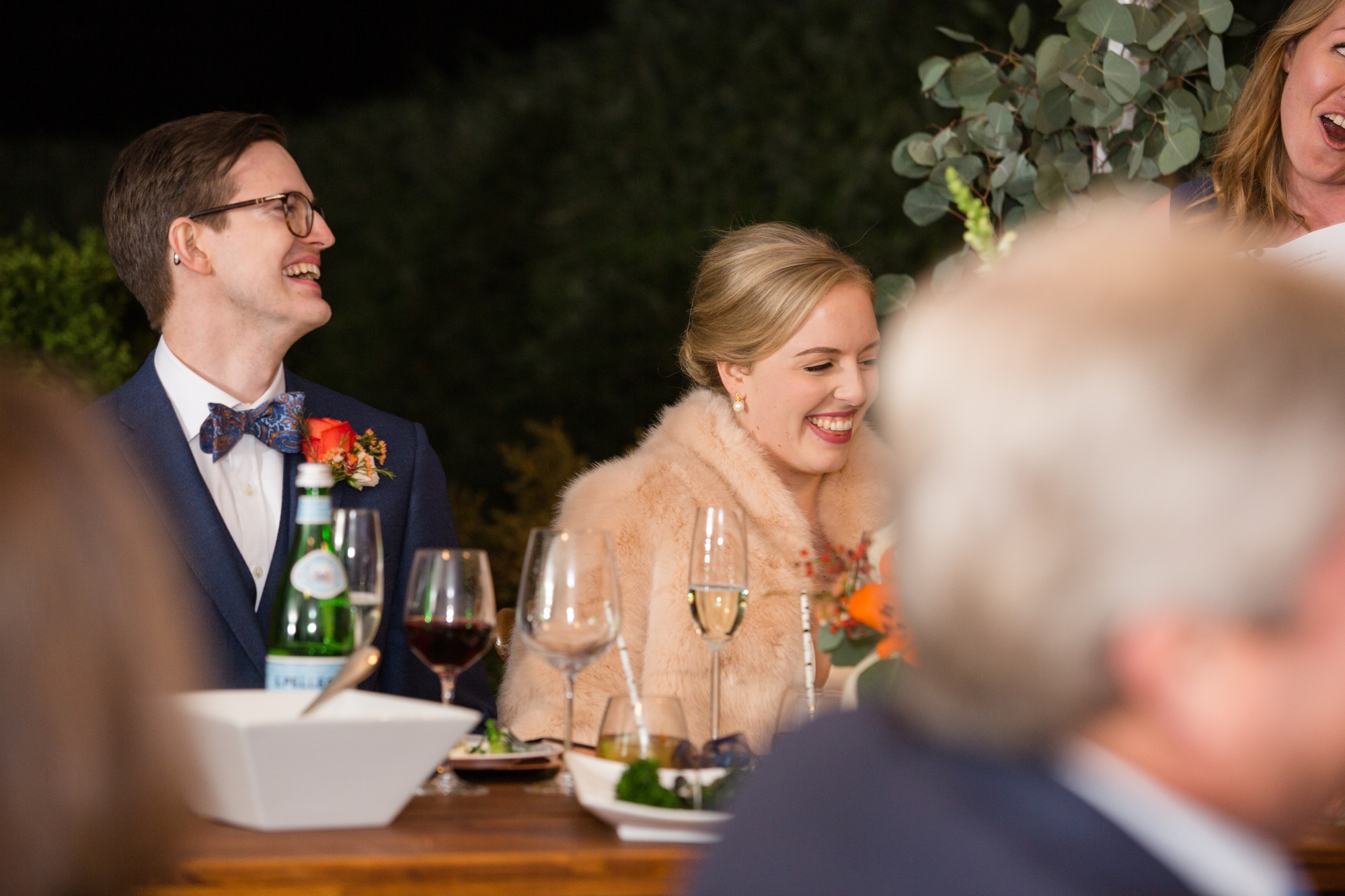 bride and groom laughing at bridesmaid toast
