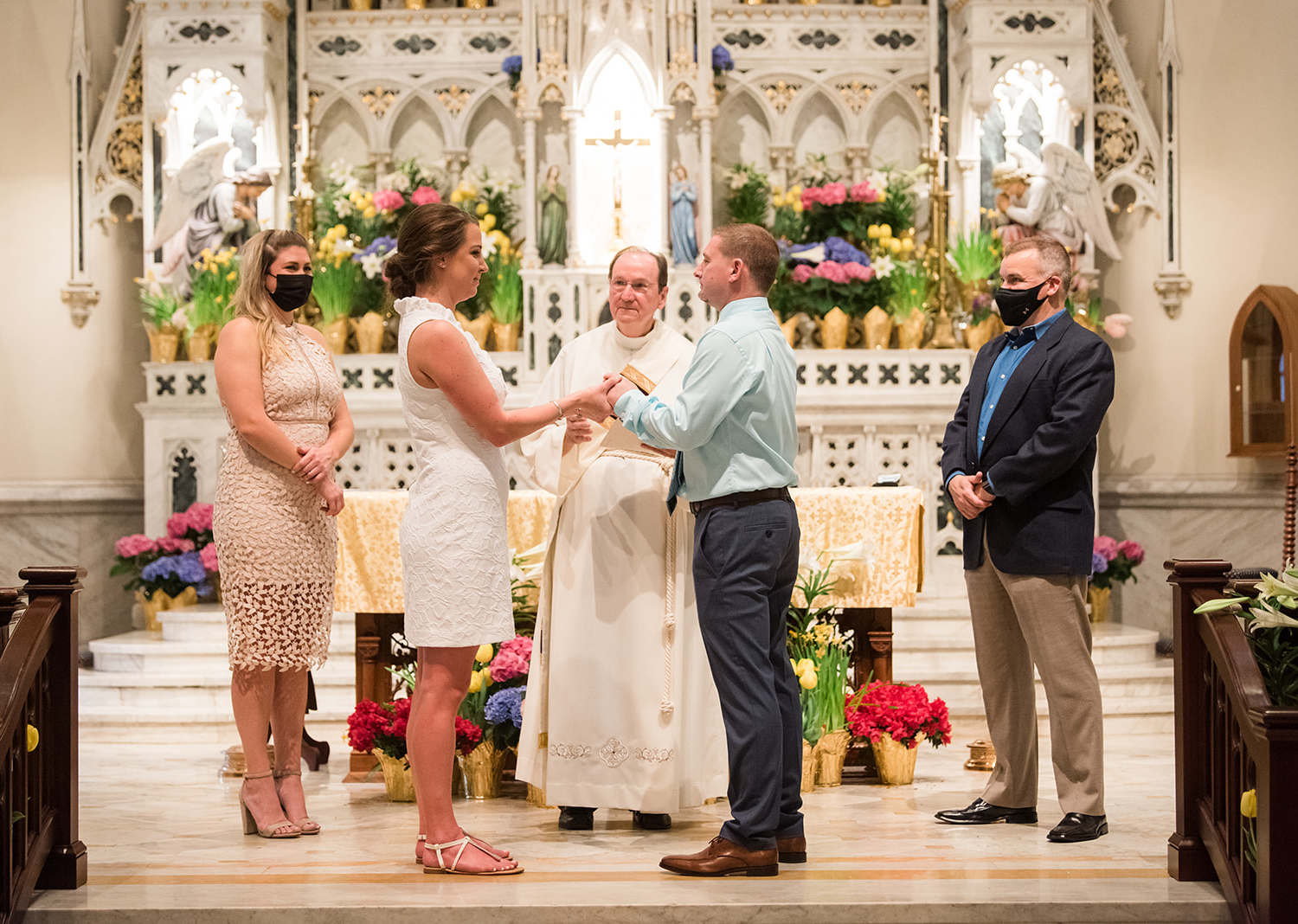 bride and groom standing in the catholic church for their wedding ceremony