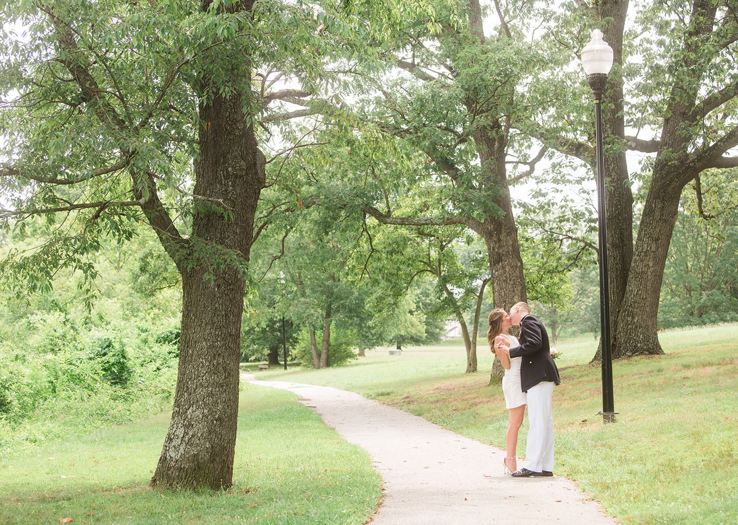 bride and groom share a kiss surrounded by green trees