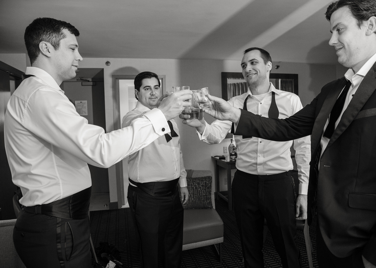 groom and groomsmen sharing a drink and a toast before the wedding