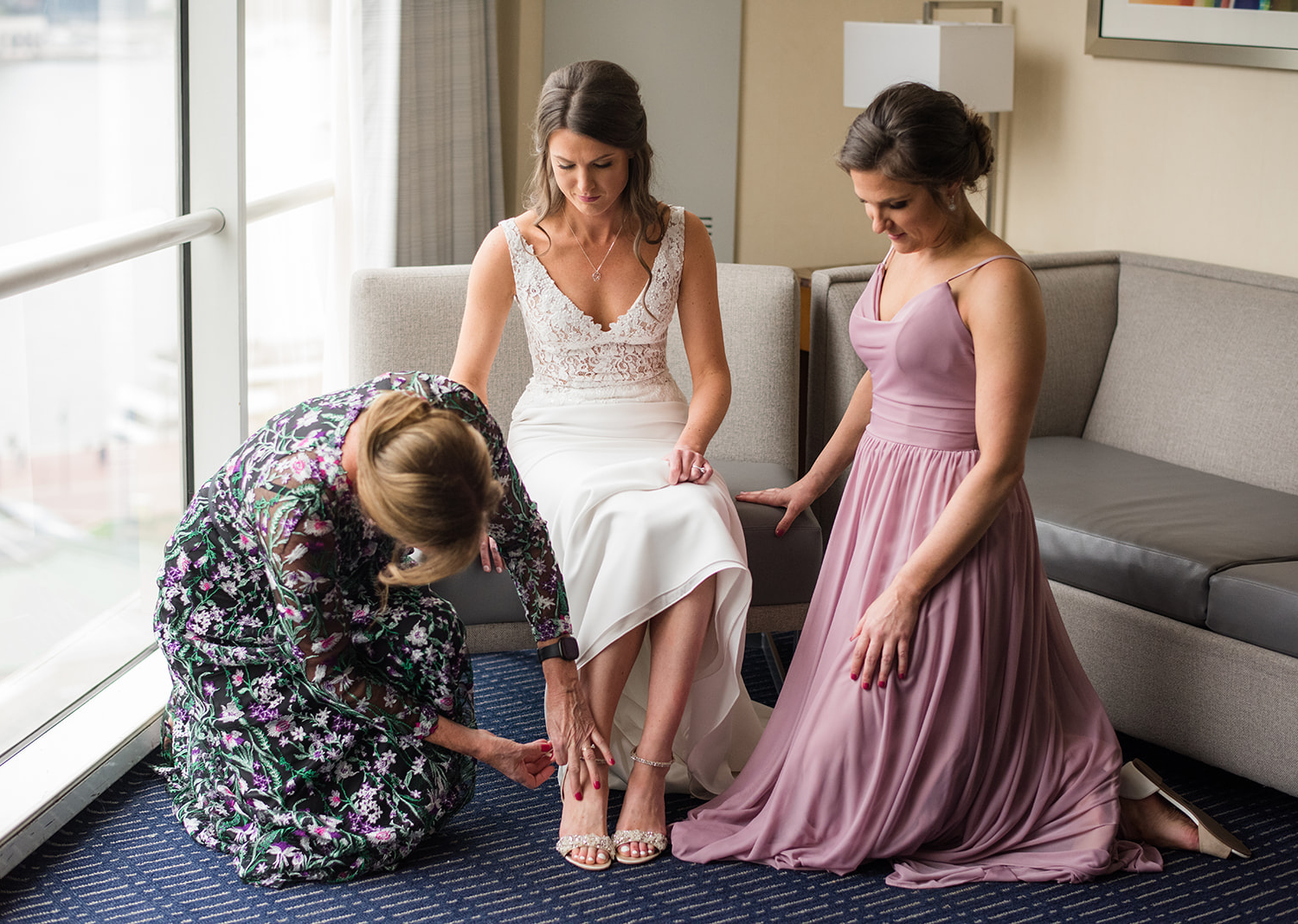 mother of the bride helping the bride put on her wedding shoes