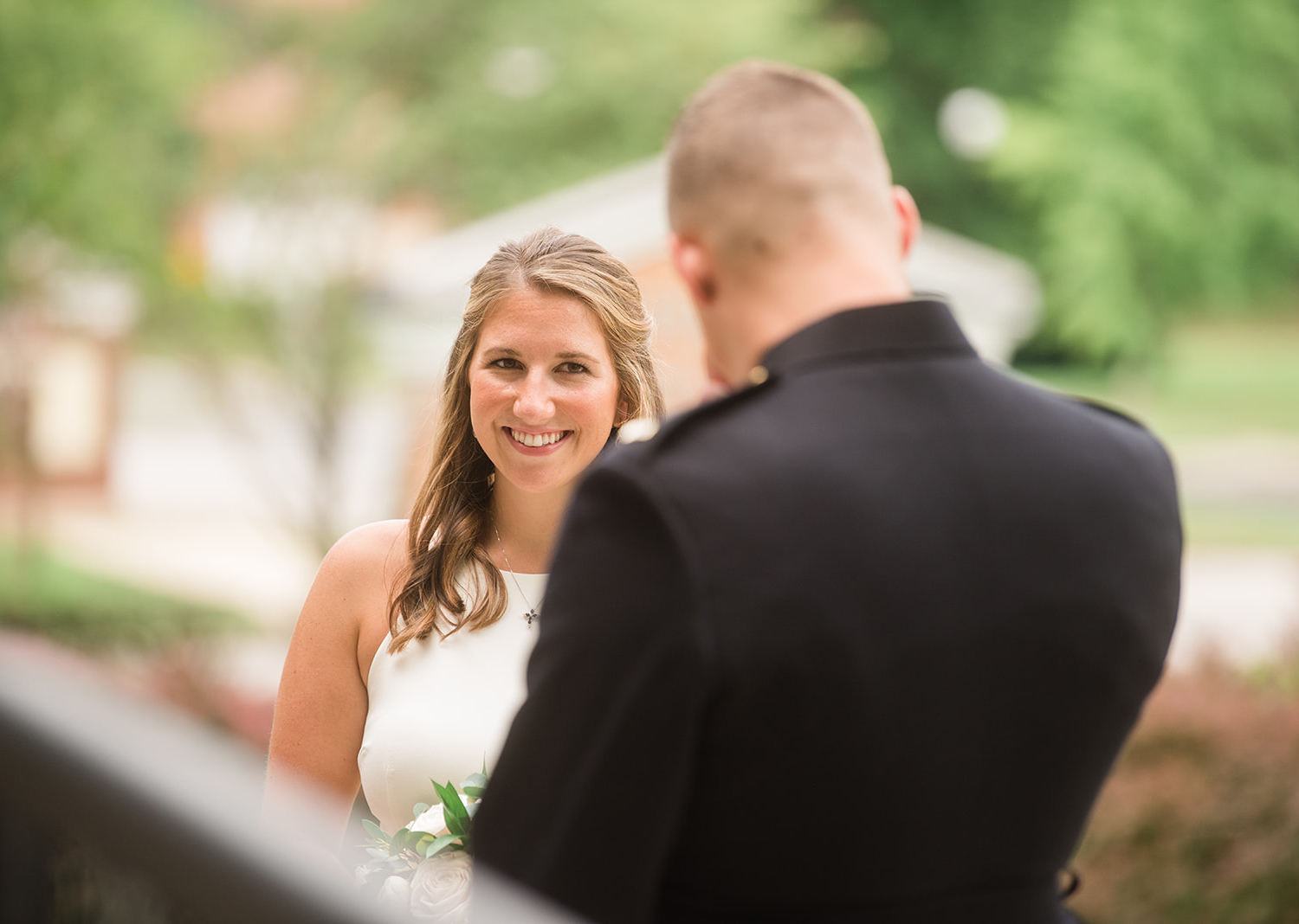 Bride smiles as she looks at the groom