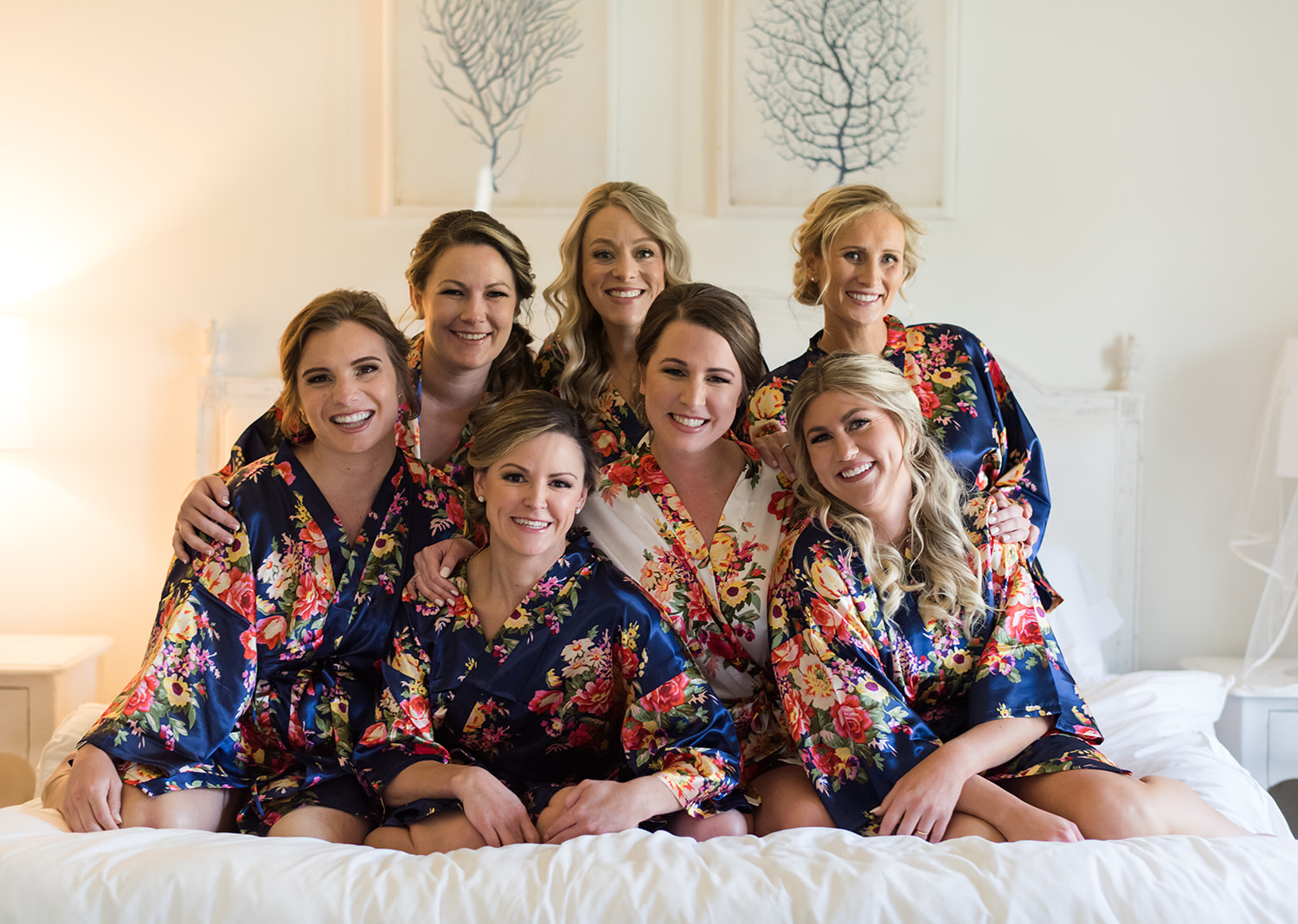 bridesmaids smiling as they all huddle up around the bride as they sit on the bed