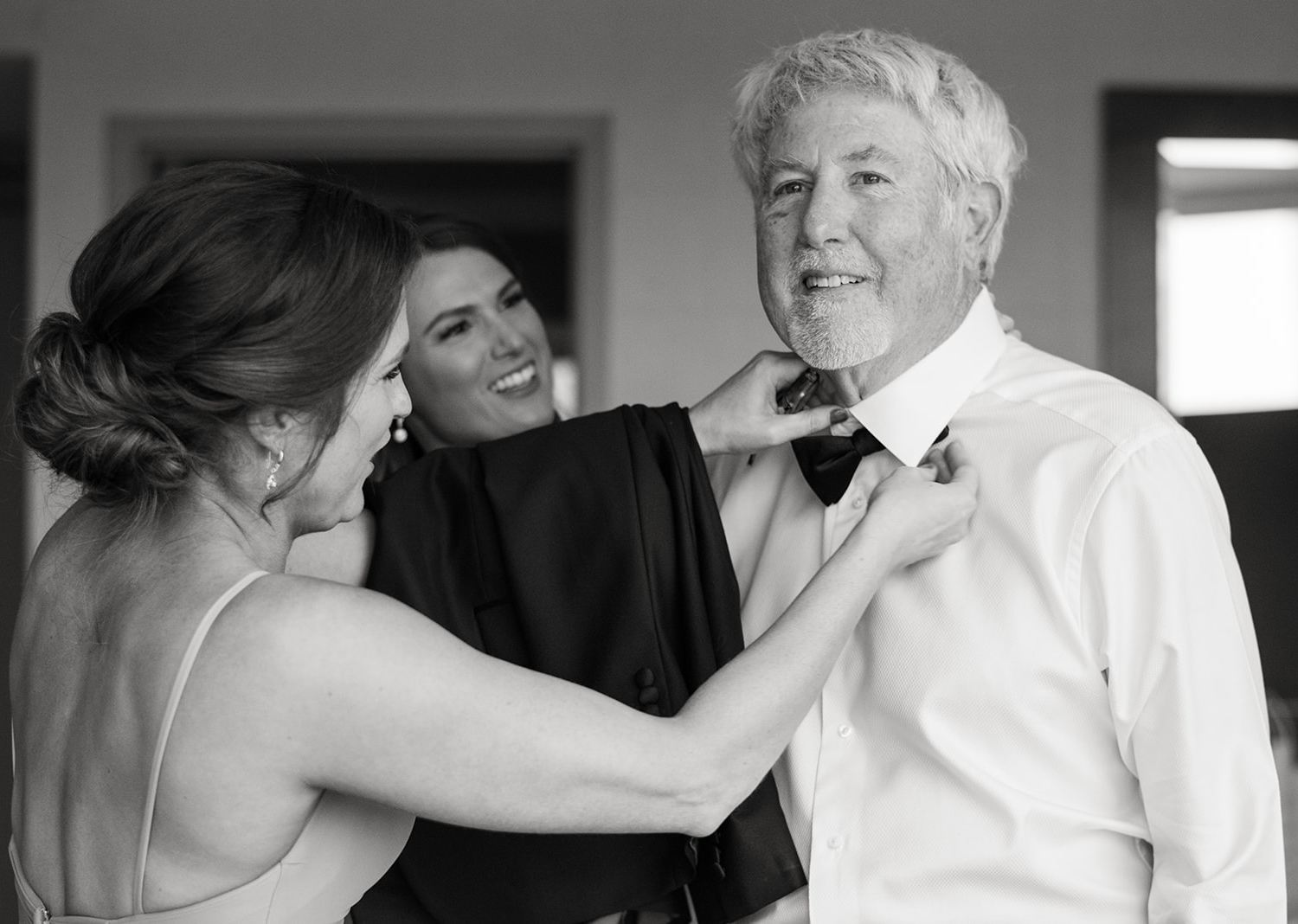 bridesmaid helping father of the bride put on his bow tie