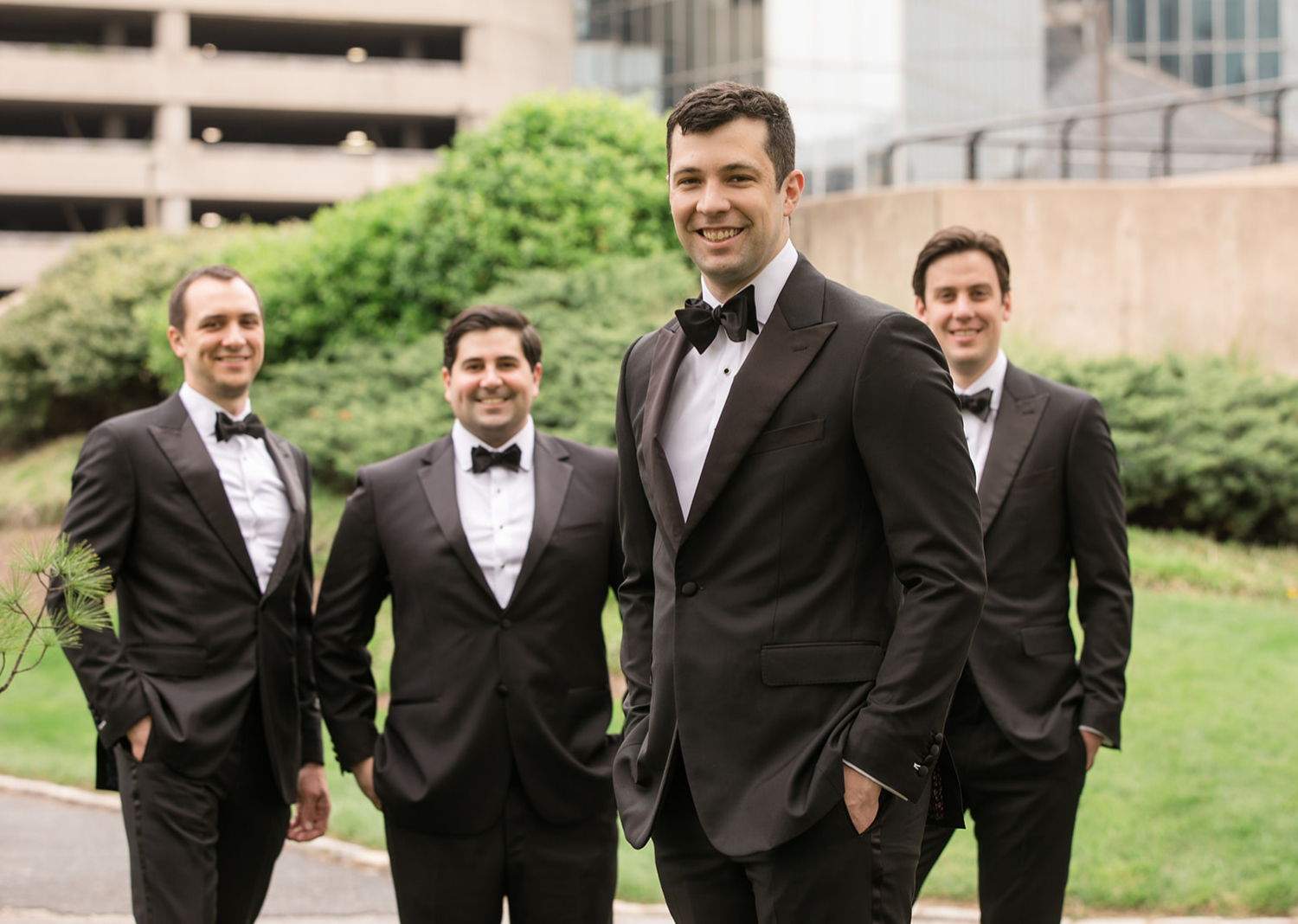 groom stands in front of the groomsmen as the groomsmen stand behind him smiling