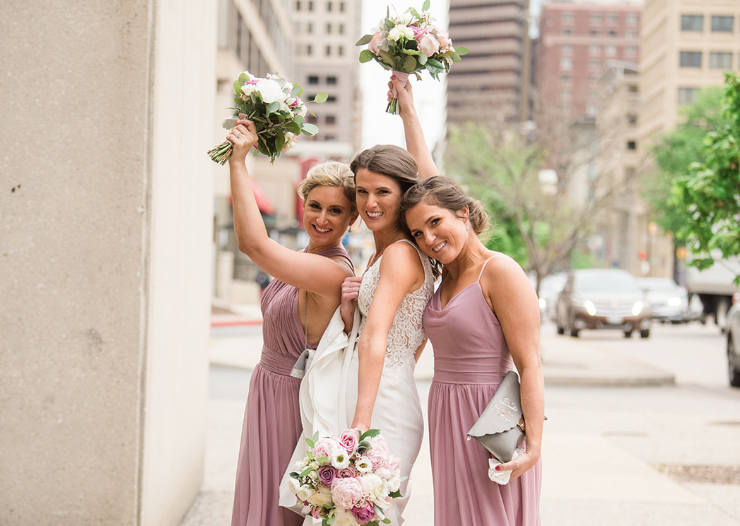 bridesmaids and bride holding their bouquet in the air smiling
