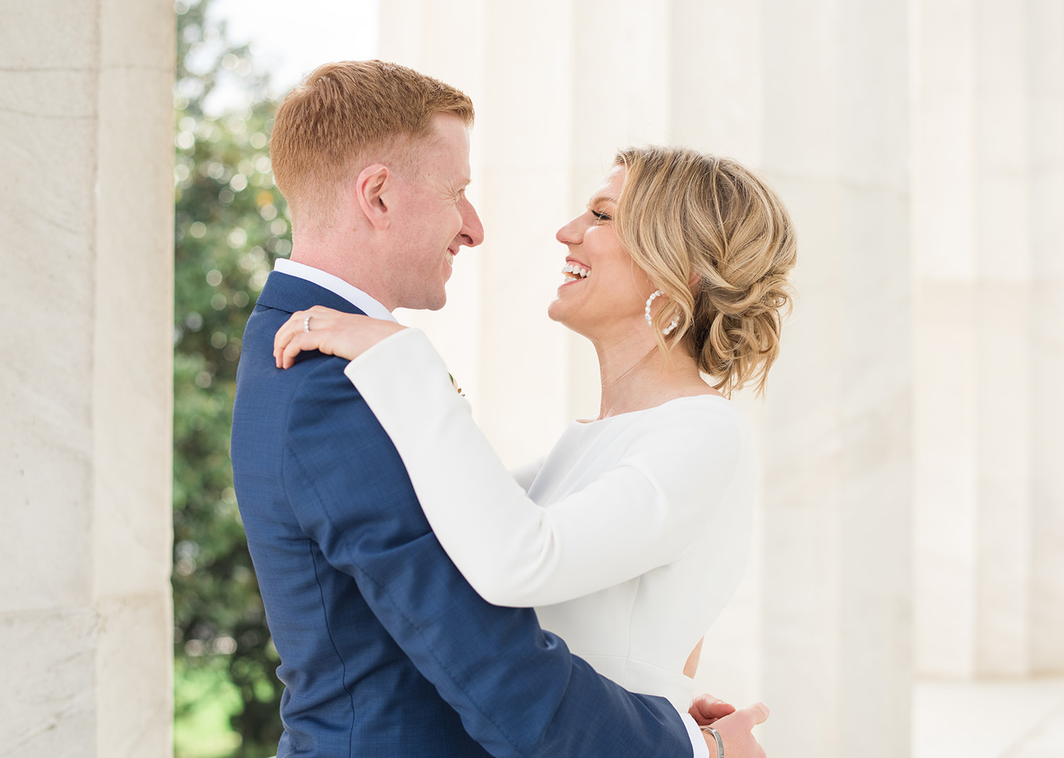 bride and groom smile as they look at eachother in the lincoln memorial