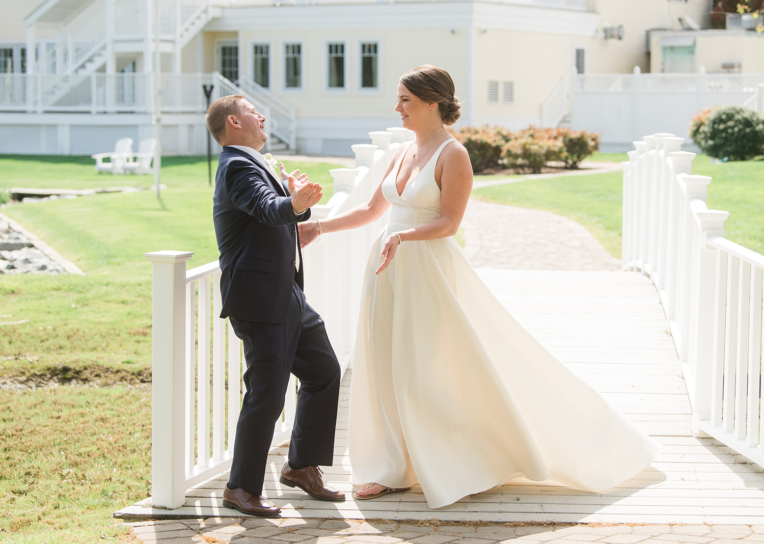 groom smiles as he sees his bride in her wedding dress for the first time