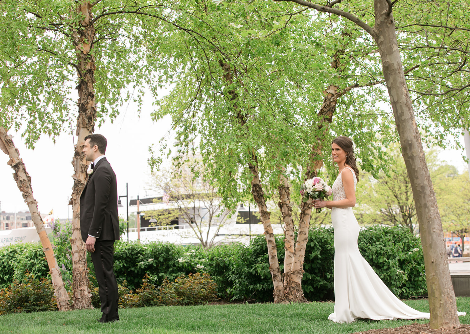 bride stands behind the groom as she approaches him for their first look