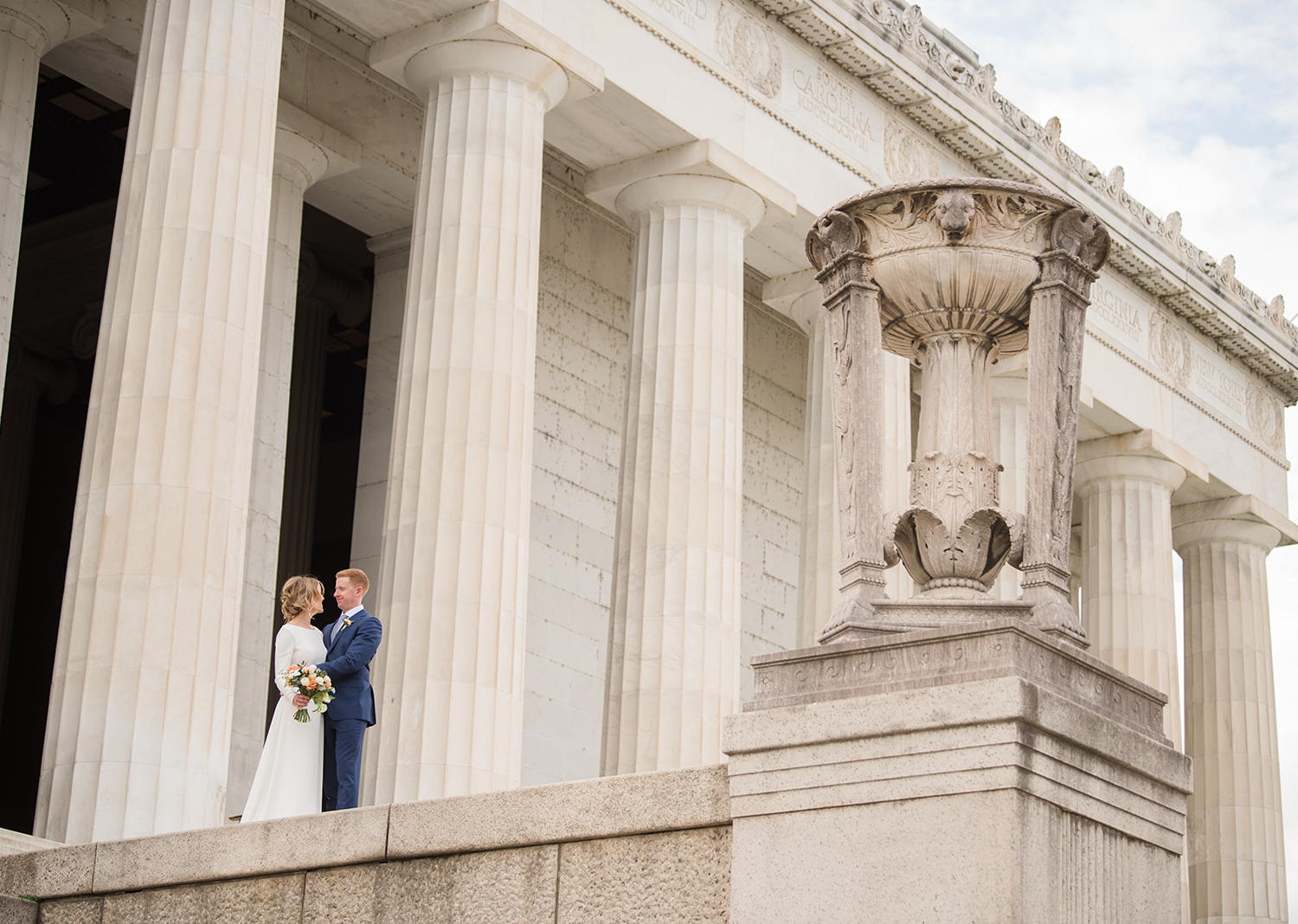 bride and groom posing in front of the lincoln memorial
