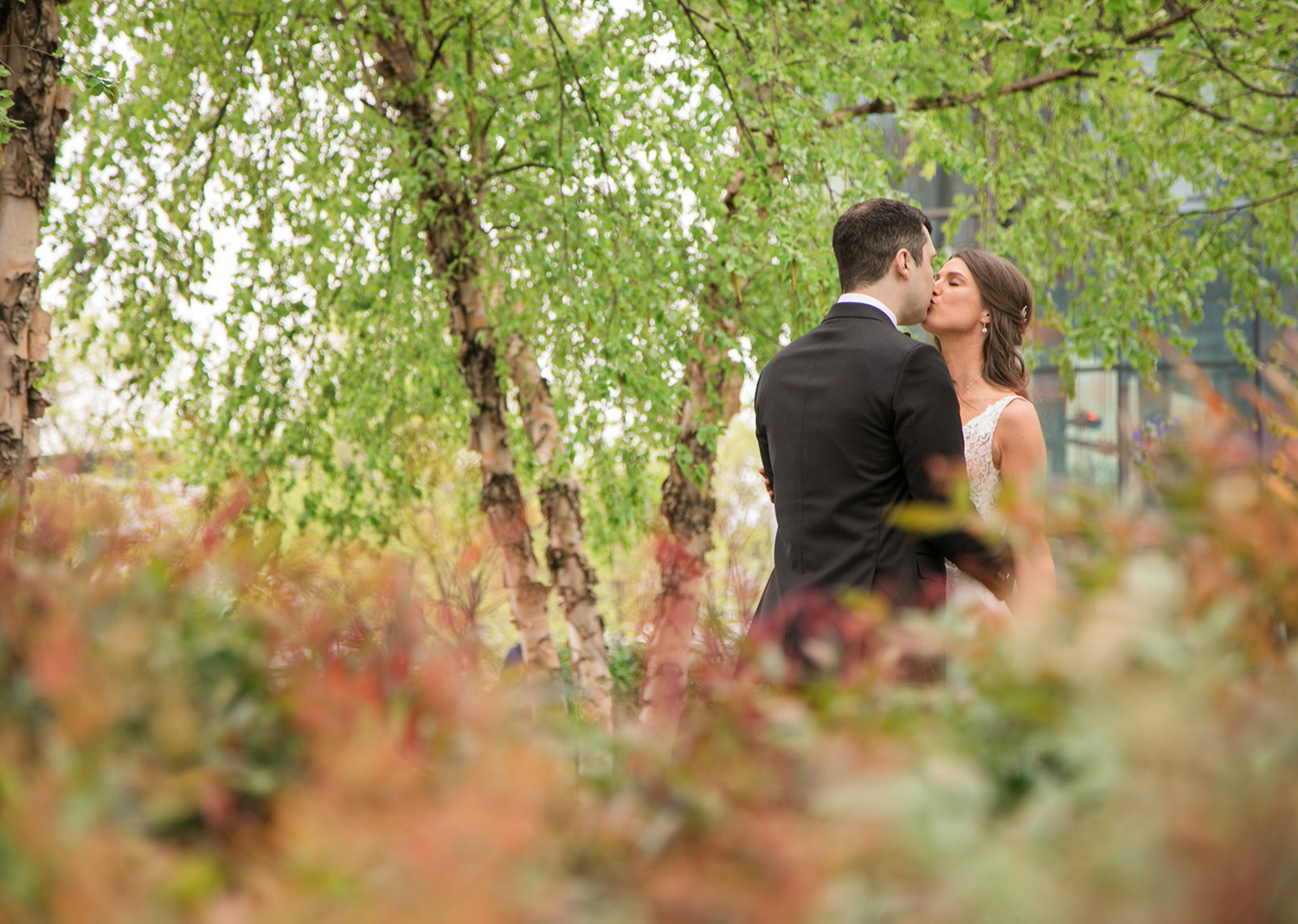 bride and groom share a kiss in a park in Baltimore