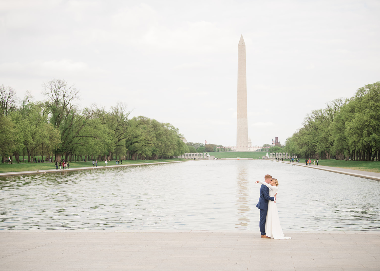 bride and groom share a kiss in front of the Washington Monument