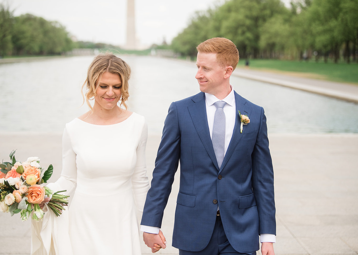 bride and groom smiling as they walk in front of the Washington Monument