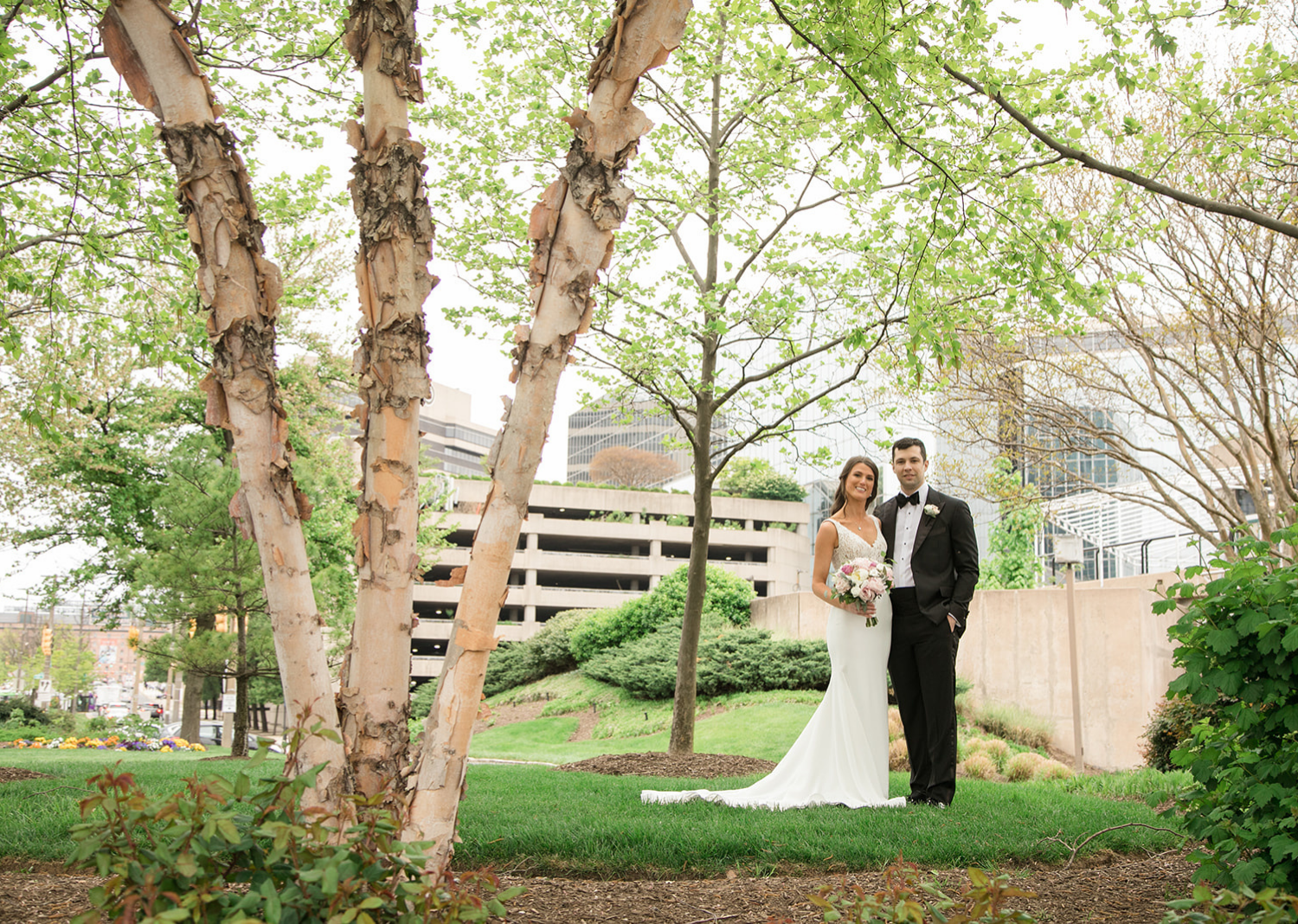 bride and groom smile as they stand in a park in Baltimore