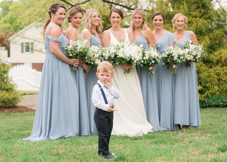 bride smiles as her bridesmaids gather around her