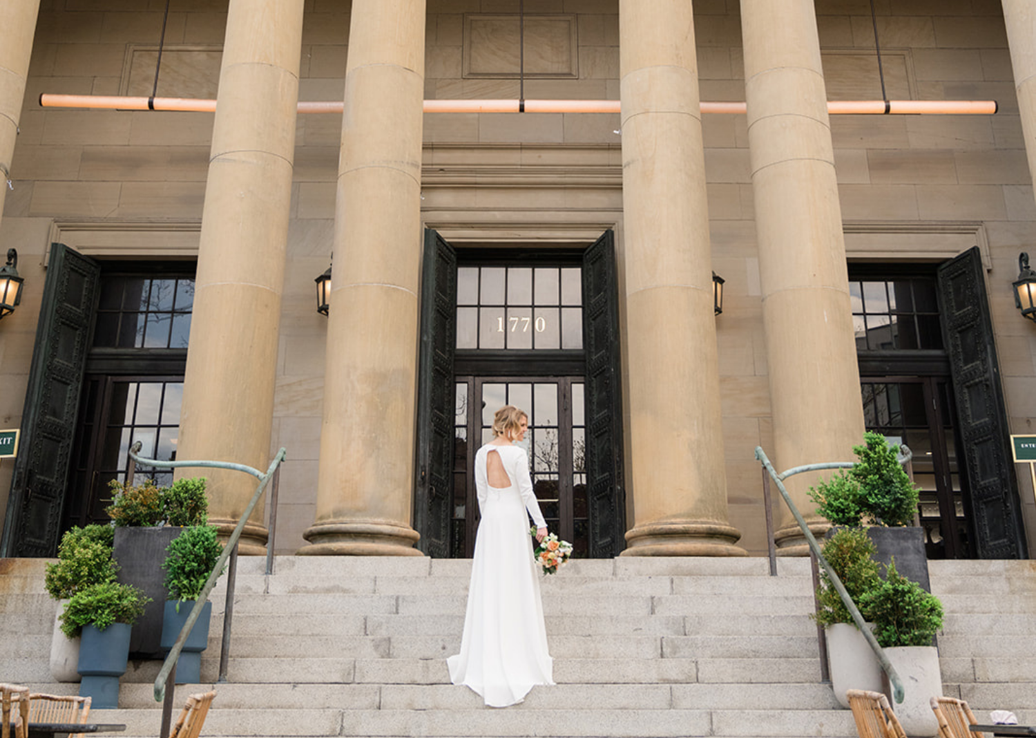 bride showing off her wedding dress as she faces away from the camera