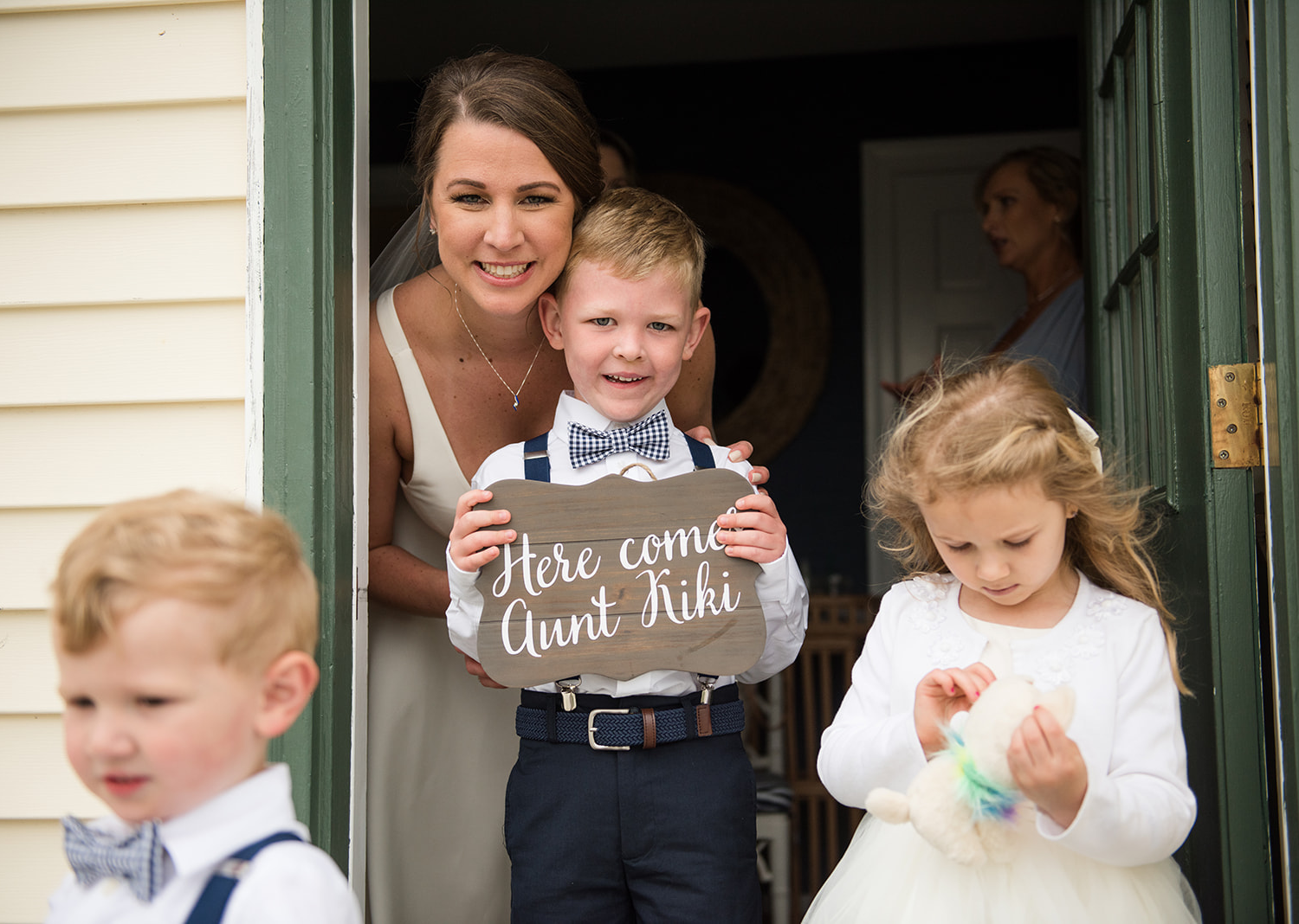 """bride smiles along with her baby groomsmen. the baby groomsmen is holding a sign that reads """"here comes aunt kiki"""""""