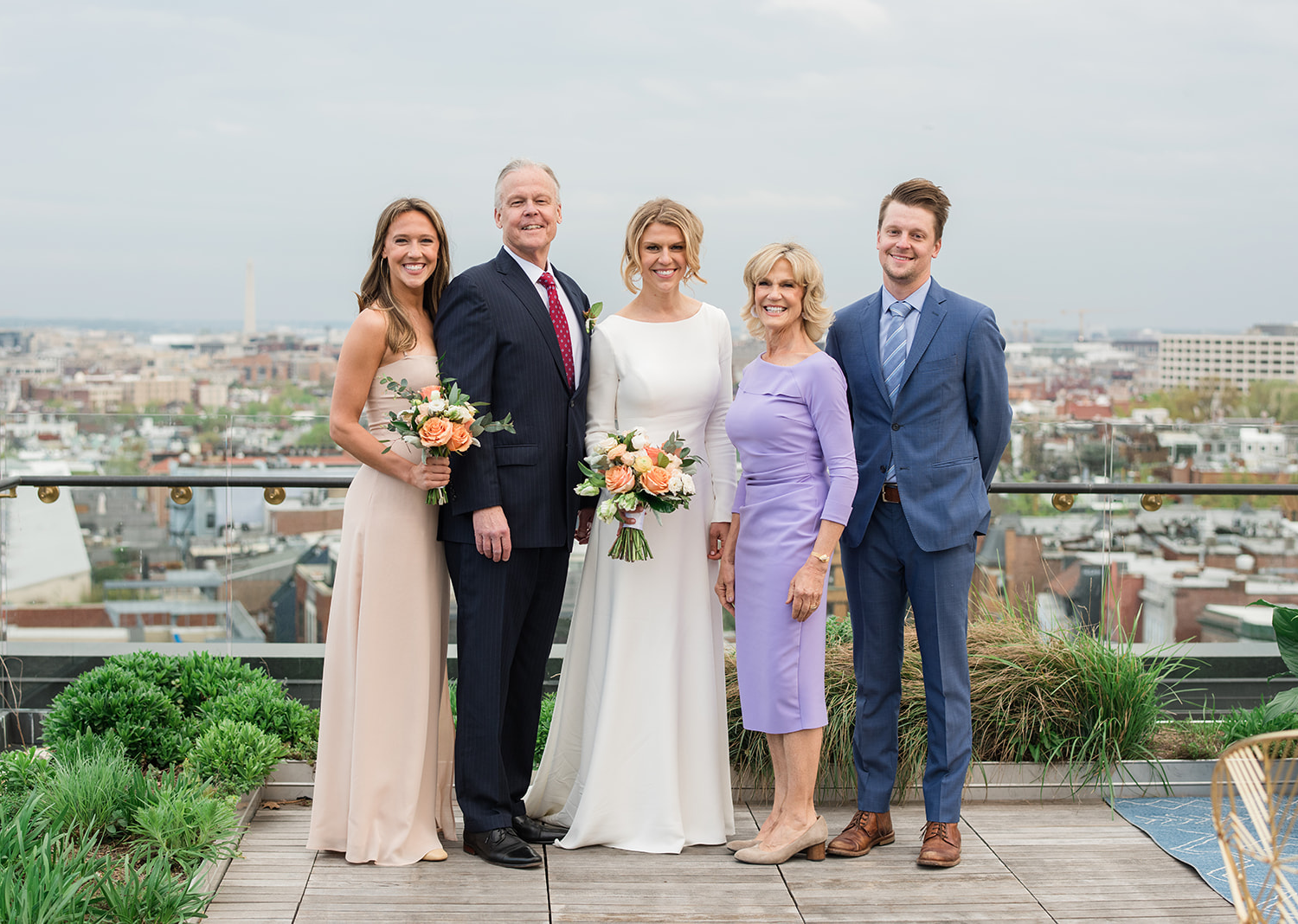 bride posing with her family on her wedding day on the rooftop of the Line hotel in Washington