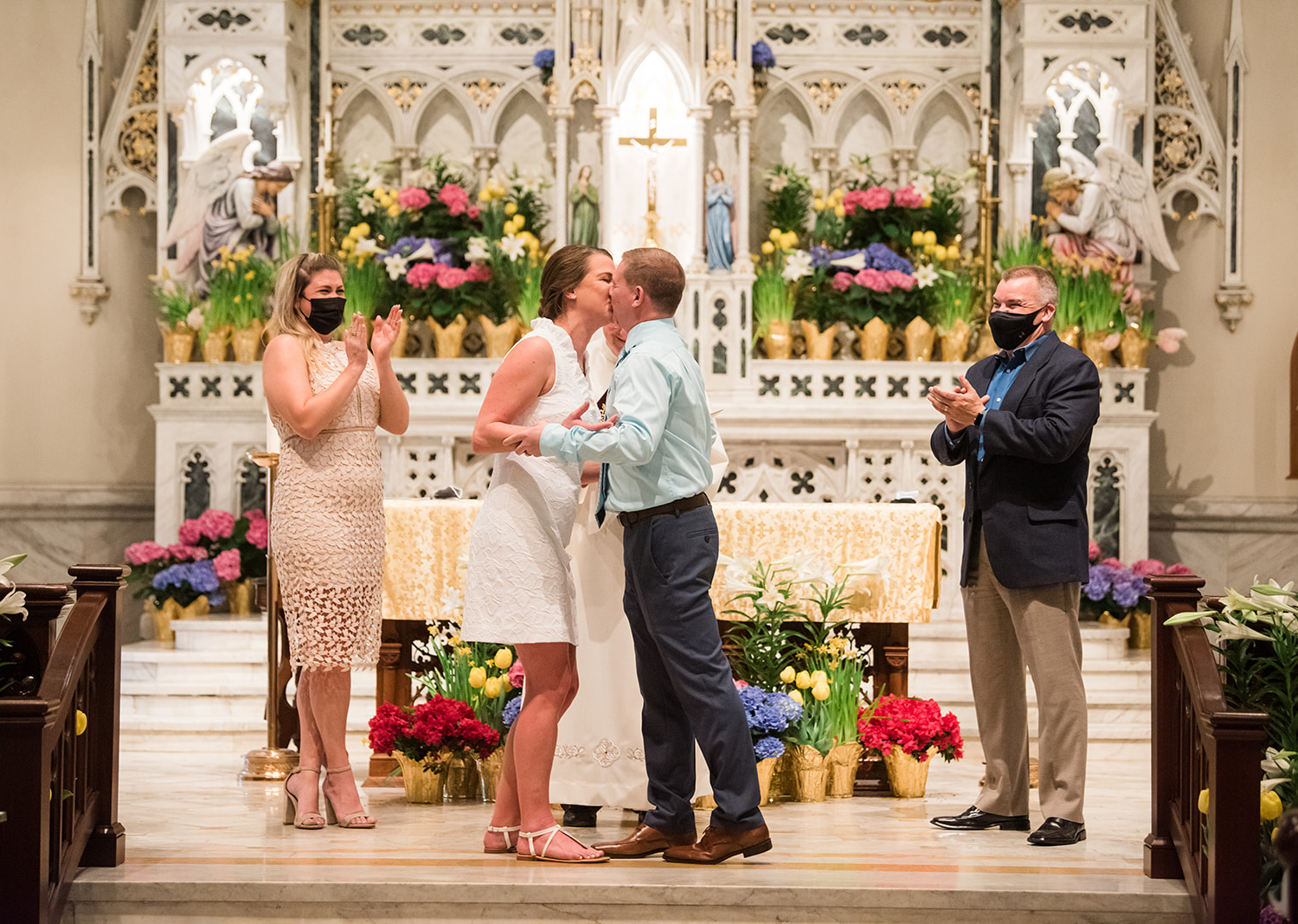 bride and groom share a kiss during their wedding ceremony in the catholic church