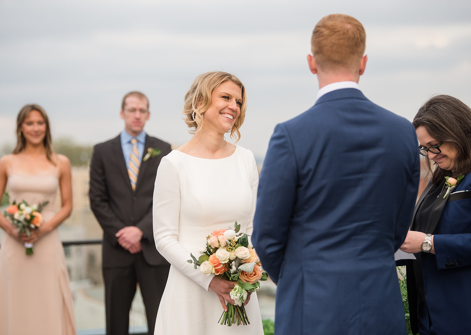 bride and groom smiling as they listen to their wedding talk on the rooftop of the line hotel in Washington
