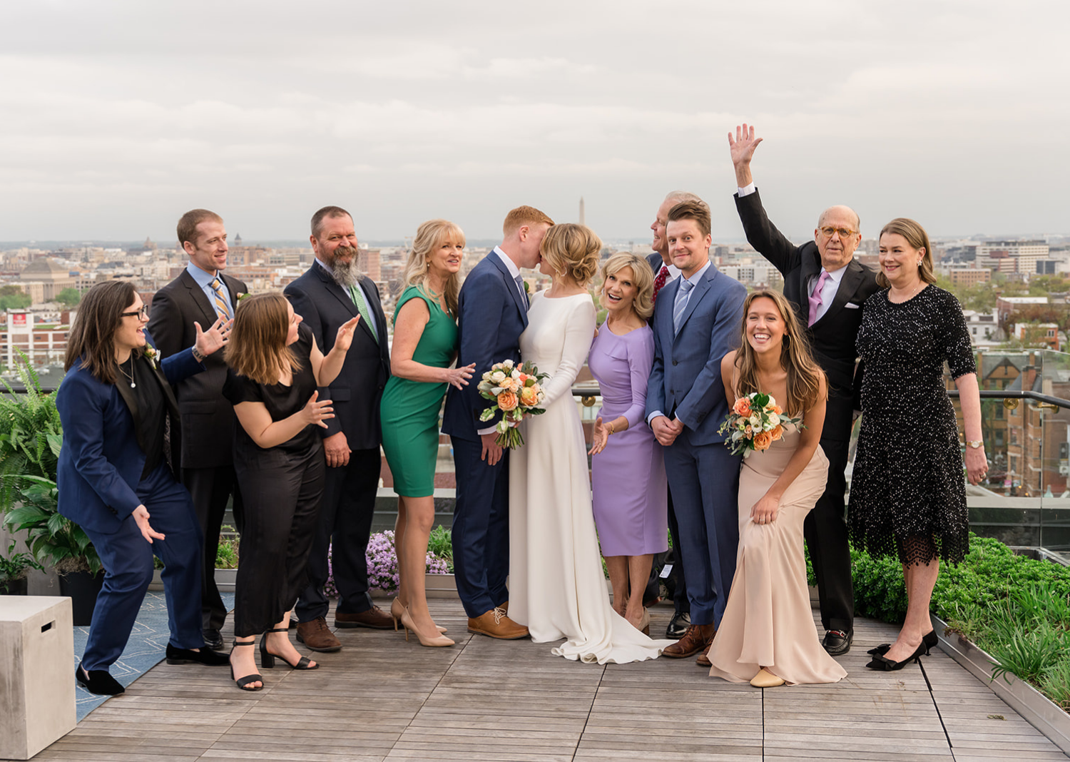 bride and groom share a kiss on the rooftop of the Line Hotel as their family gathers around them celebrating