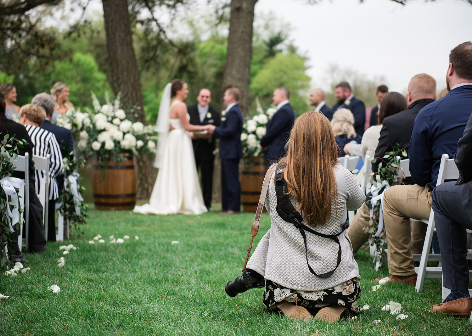 bride and groom during their wedding ceremony as their wedding photographer kneels down to grab the perfect angle