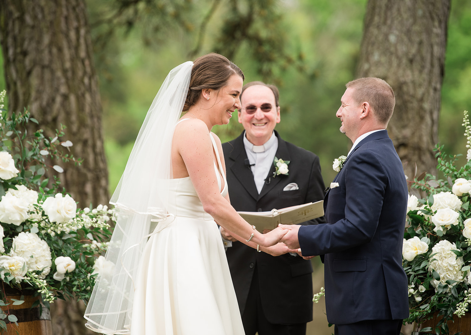 bride and groom smile during their wedding ceremony