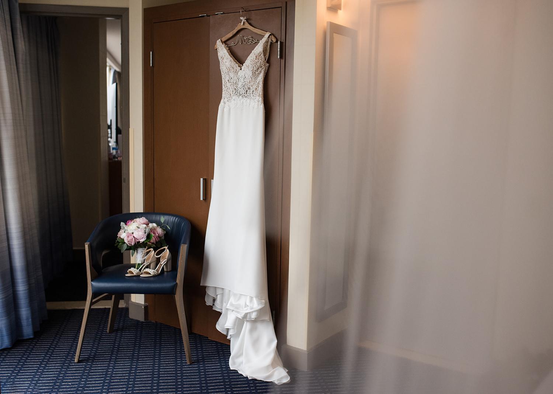 wedding dress hanging over door of bridal suite