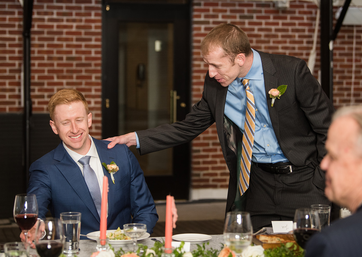 groom smiles as one of his groomsmen shares a speech during their wedding reception