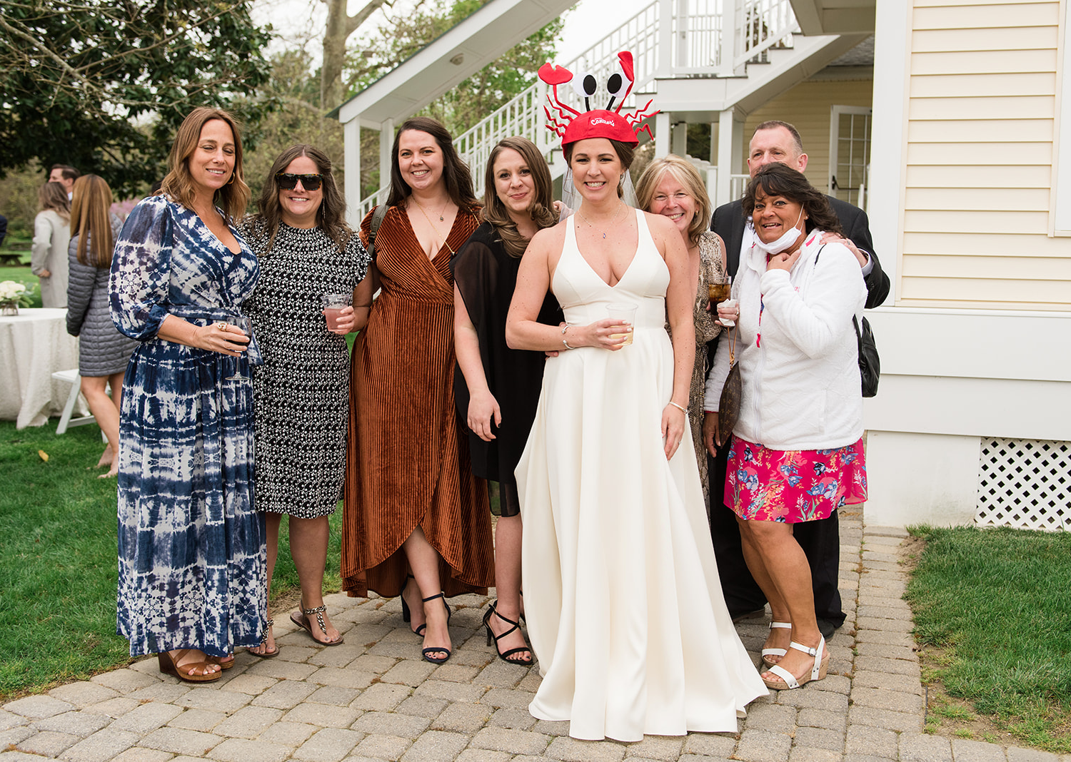 bride is wearing a funny crab hat as she is surrounded by her friends and family