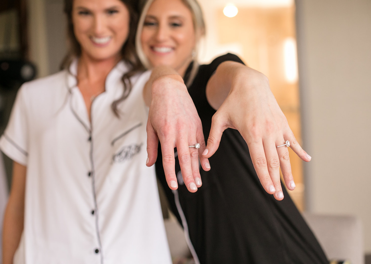 bride and bridesmaid showing off their engagement rings