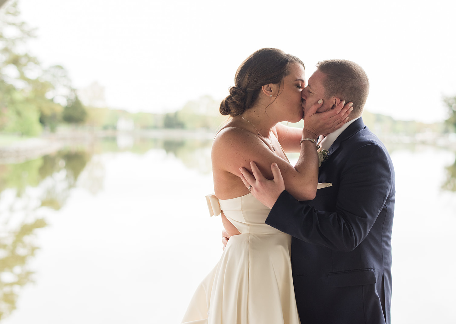 bride and groom share a kiss in front of the river