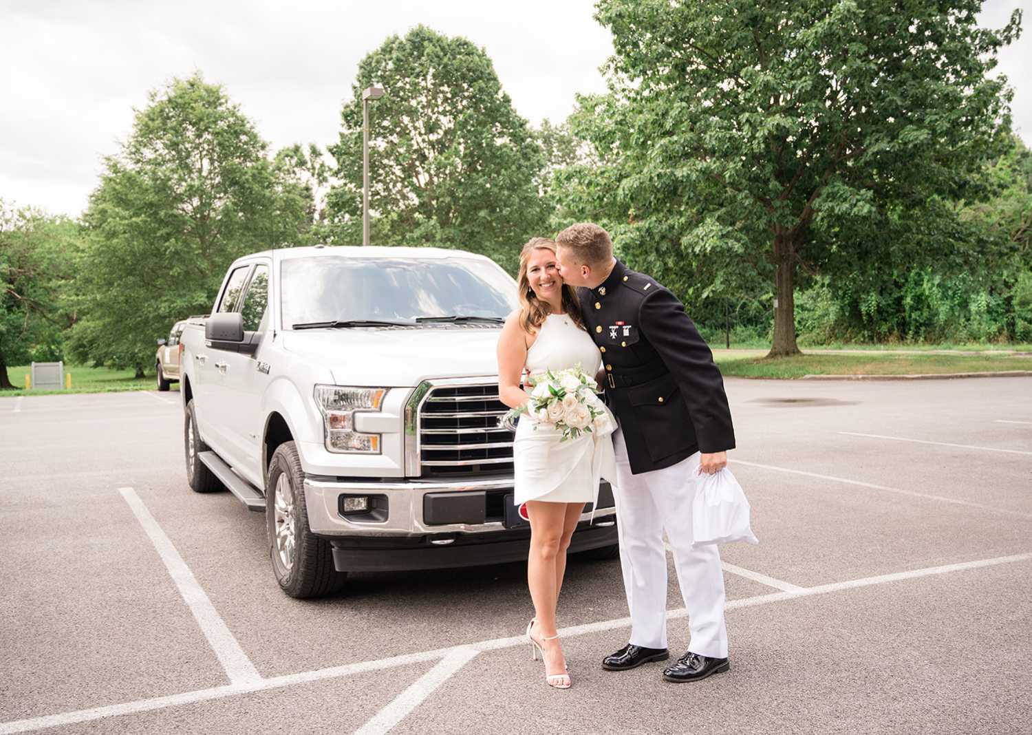 groom kisses his bride on the cheek as they pose i front of their white truck