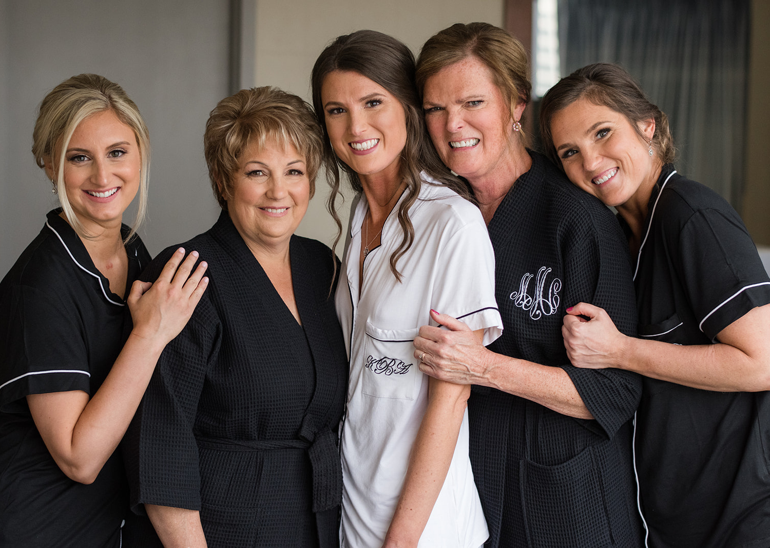 bride smiling with her bridesmaids and mother of the bride