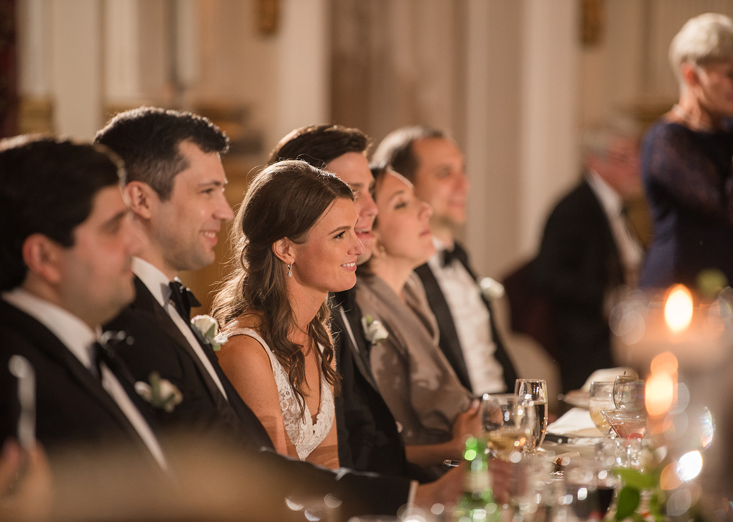 bride and groom smile as they hear speeches from their friends and family