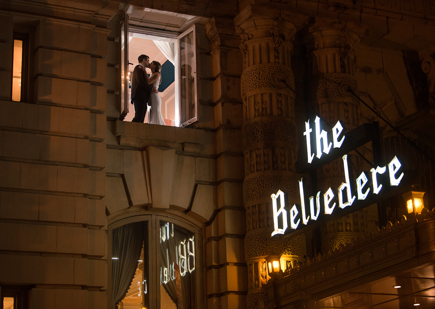 bride and groom share a kiss as they are photographed through a window of the Belvedere hotel