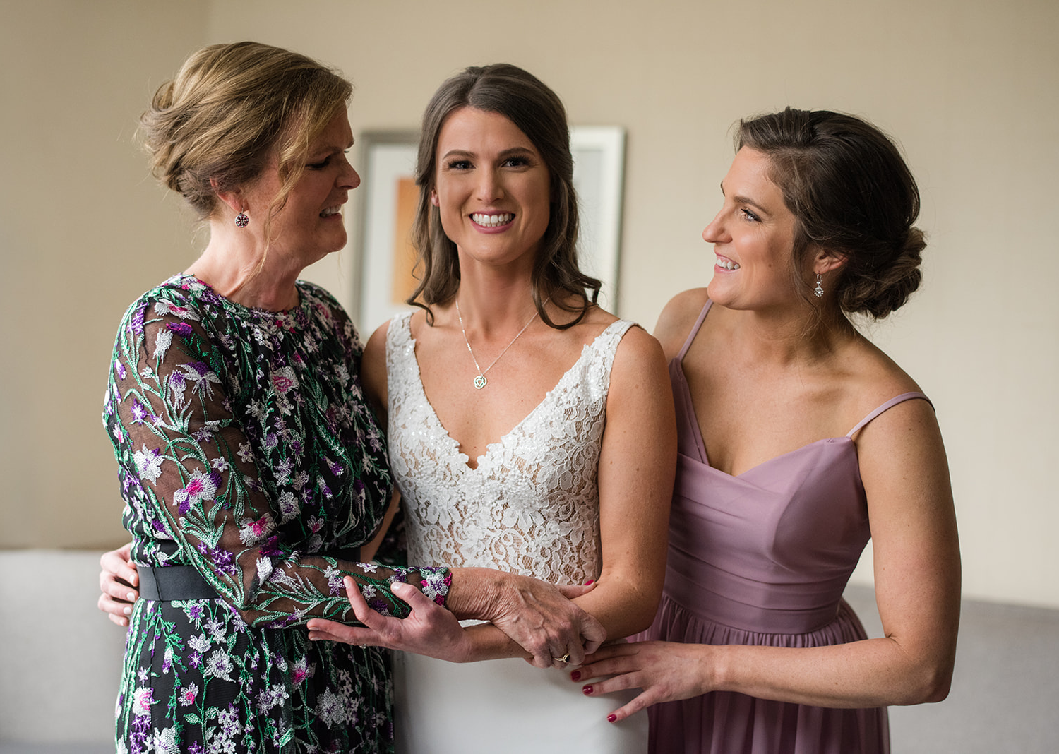 bride posing with her mother and bridesmaid